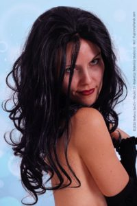 model with a sinthetyc wavy black wig in fornt of a light blue background