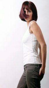 la modella posa con la sua acconciatura naturale davanti ad uno sfondo bianco.