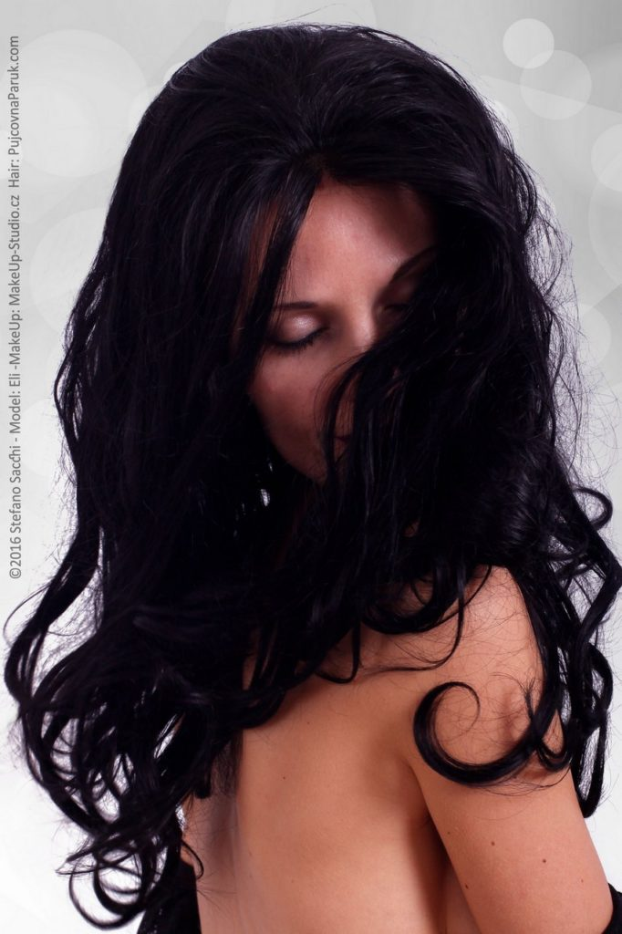 the model with eyes closed is wearing a cinema style professional lacefront wig, black